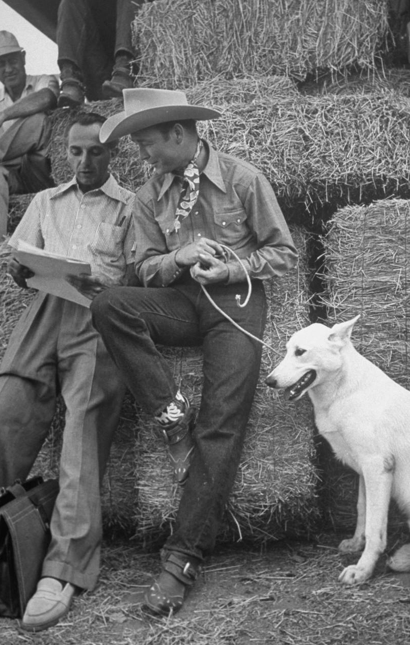 """Actor Roy Rogers & his dog """"Phantom talking to his agent during break in filming on the Republic Pictures movie lot.  Hollywood, ca. 1939."""