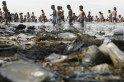People paddle in the waters of Manila Bay amid garbage in the Philippines' capital city on Easter Sunday, April 24, 2011.