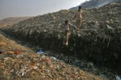 Waste collector Dinesh Mukherjee, 11, watches his friend jump over a puddle of toxic liquid at the Ghazipur landfill in New Delhi Nov. 10, 2011.