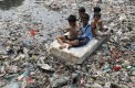 Children sitting on a makeshift raft play in a river full of rubbish in a slum area of Jakarta, Indonesia, in 2012.