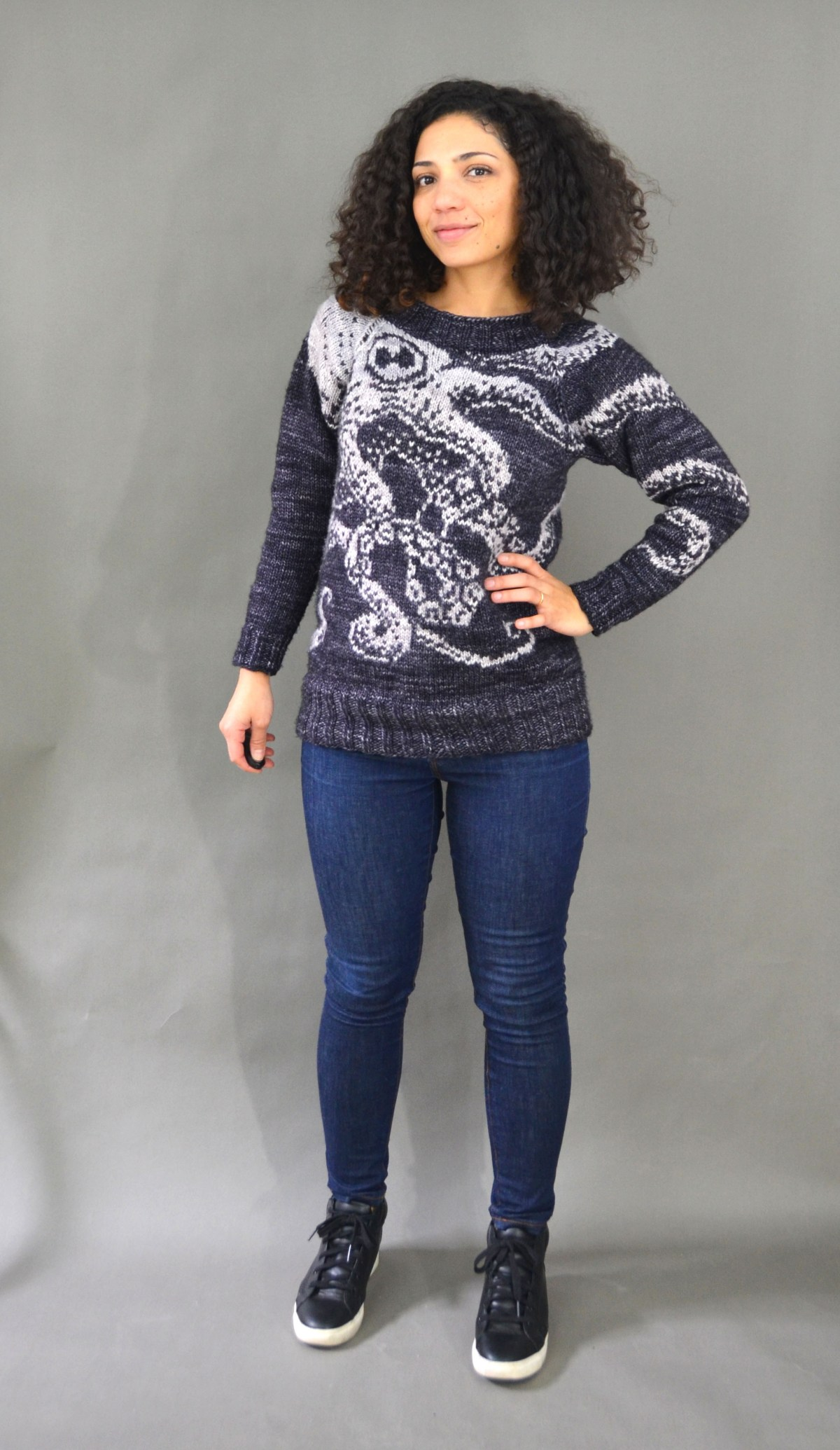 The author looking at the camera with one hand on her hip and smiling.  She is wearing a grey and white knitted jumper with an octopus on it, blue jeans and black sneakers.