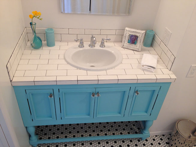 An image of a vanity which is tiled in white subway tiles.  The doors and frame of the cabinet are painted light blue.