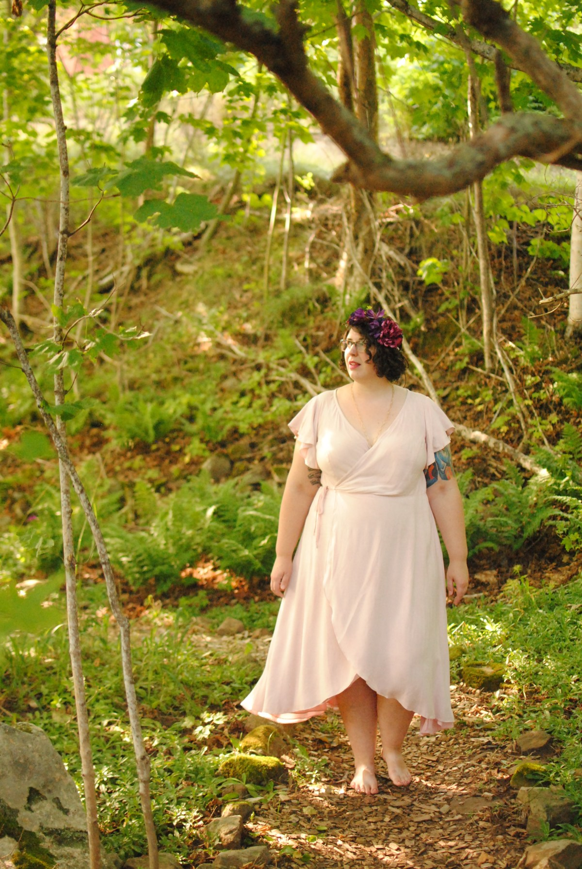 Shannon, a fat, White person, standing in the woods wearing a pale pink wrap dress and a flower crown. The tone of the image is warm and summery.