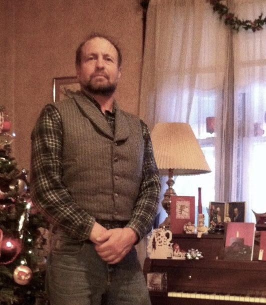 The author's uncle in a grey pinstripe vest, standing by Christmas decorations