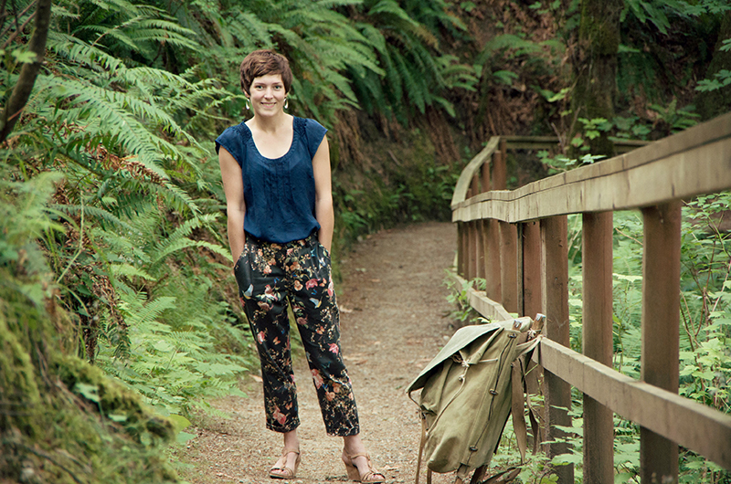 Morgan standing in a fern gully wearing floral Jedediah trousers with her hands in her pockets.