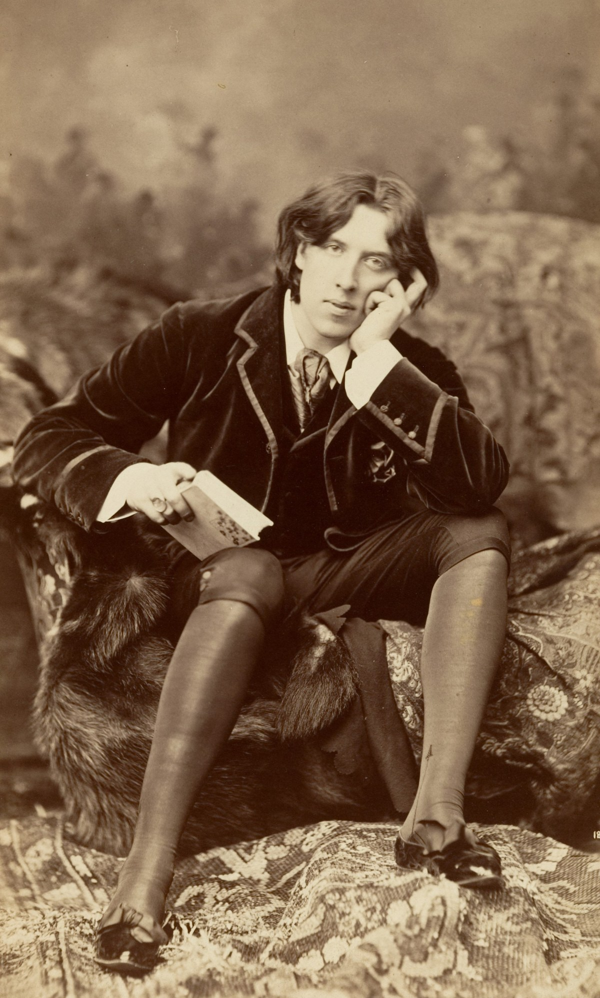 Oscar Wilde, seated, wears a velvet jacket, hose, and breeches. He holds a book and gazes at the camera.