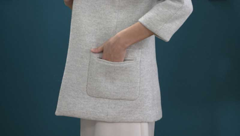 Photograph of a woman putting her hand in the pocket of her grey jacket which has a welt pocket