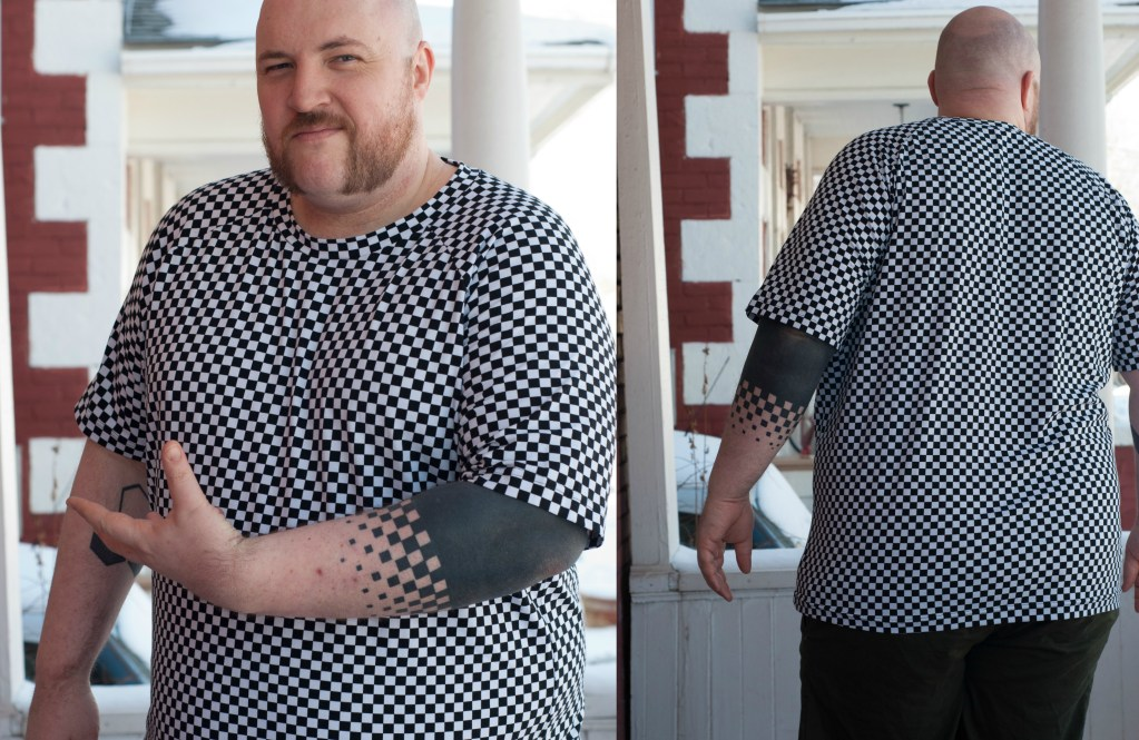 Jamie shows off the black and white tee, with a checkerboard print that matches his new arm tattoo.