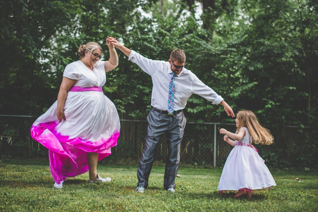 L-R: A woman wearing a white, short-sleeved, full-skirted dress with a hot pink waistband and a hot-pink dip-dyed effect on the hem, with sneakers. A man, in a dress shirt, tie, and metallic gray dress pants, holds one of the woman's hands, and reaches out to a little girl in a white dress with long full skirt and pink waist sash who is twirling and laughing.
