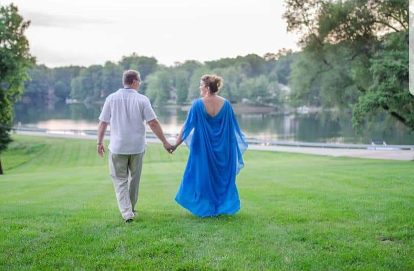 The woman in the drapey blue dress walks away from the camera, hand in hand with a man in a white shirt and chinos. Her gown has an integrated cape that falls from her shoulders and streams out behind her.