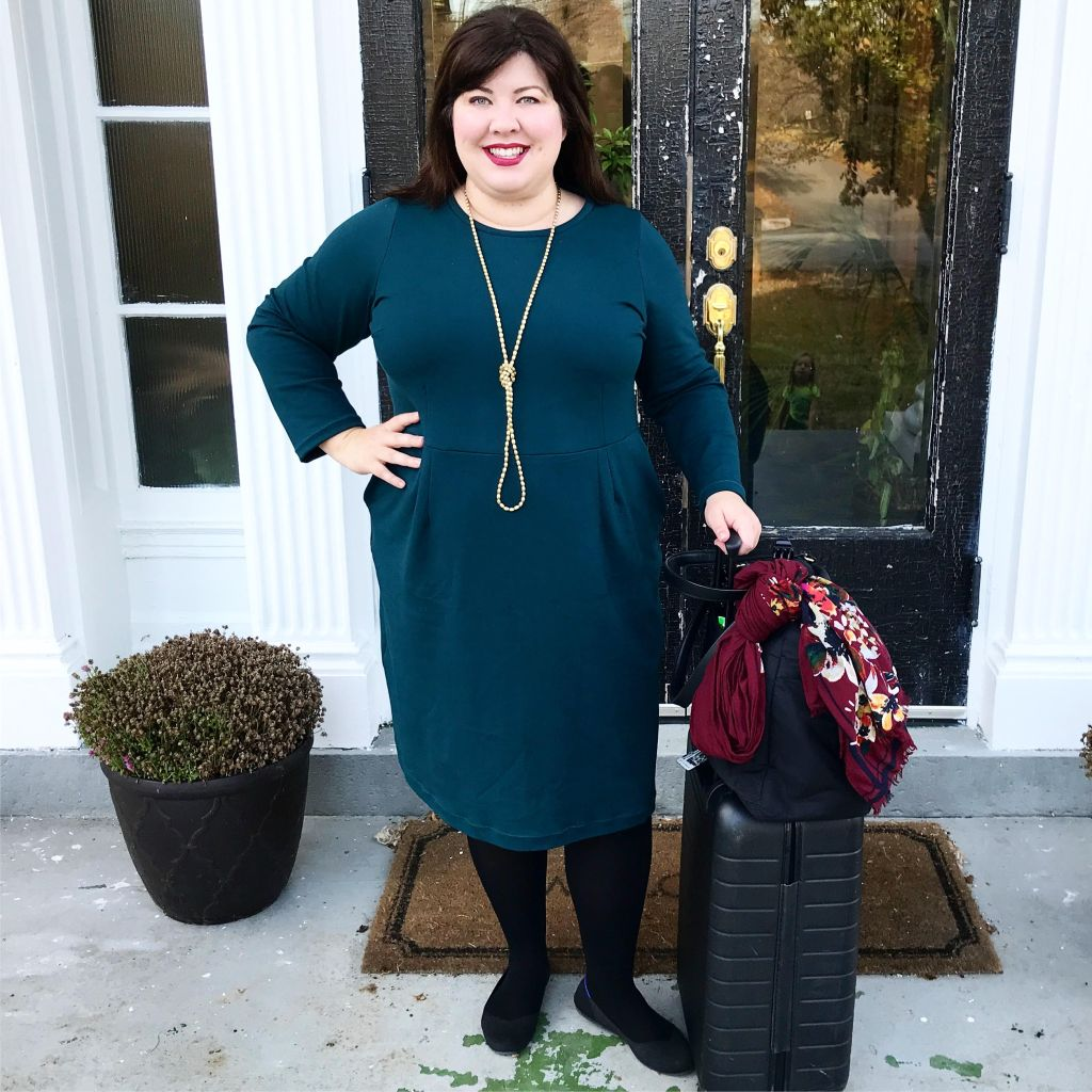 Picture of Jennifer wearing a dark teal Rivermont dress.  She has a suitcase next to her ready to go on another work trip.
