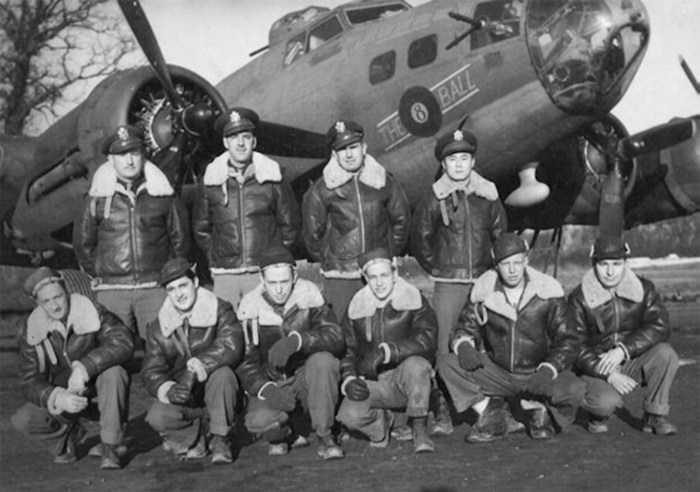 A black and white photo of nine white men wearing leather and sheepskin uniform pilots jackets, lined up in front of a World War II propeller plane.