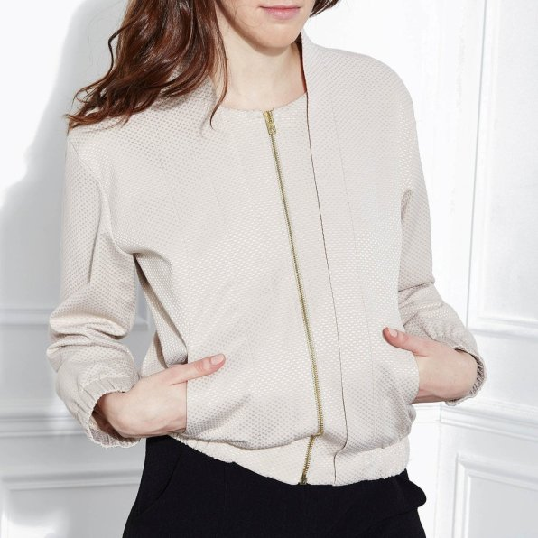 A white woman wears a beige, textured woven bomber jacket with vertical seams on the bodice front and elastic at the wrists and waist.