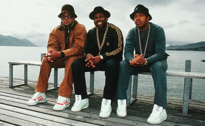 Three black men, the members of Run-DMC, are seated on a bench in front of a body of water. They each wear a bucket hat, monochrome track suit, and white sneakers.