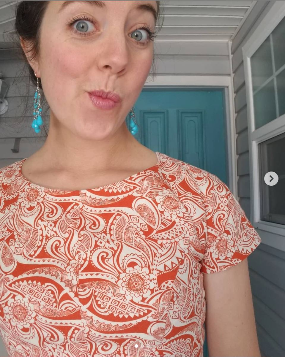 Orange top with floral design in white
