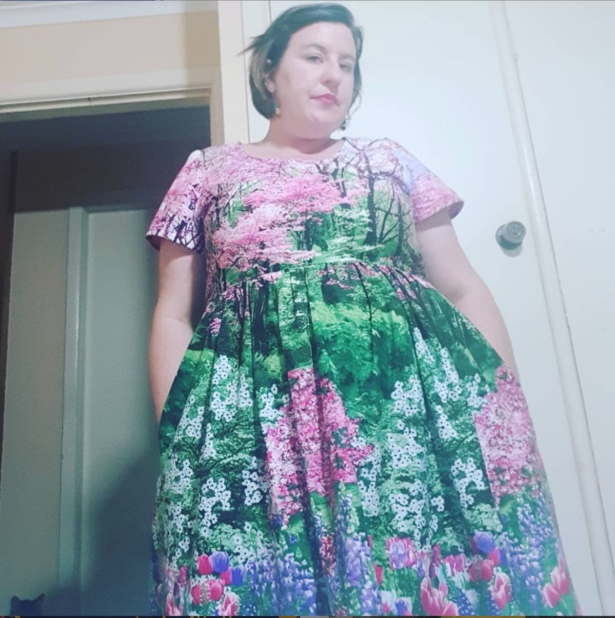 Pink and green dress with flower scene on it