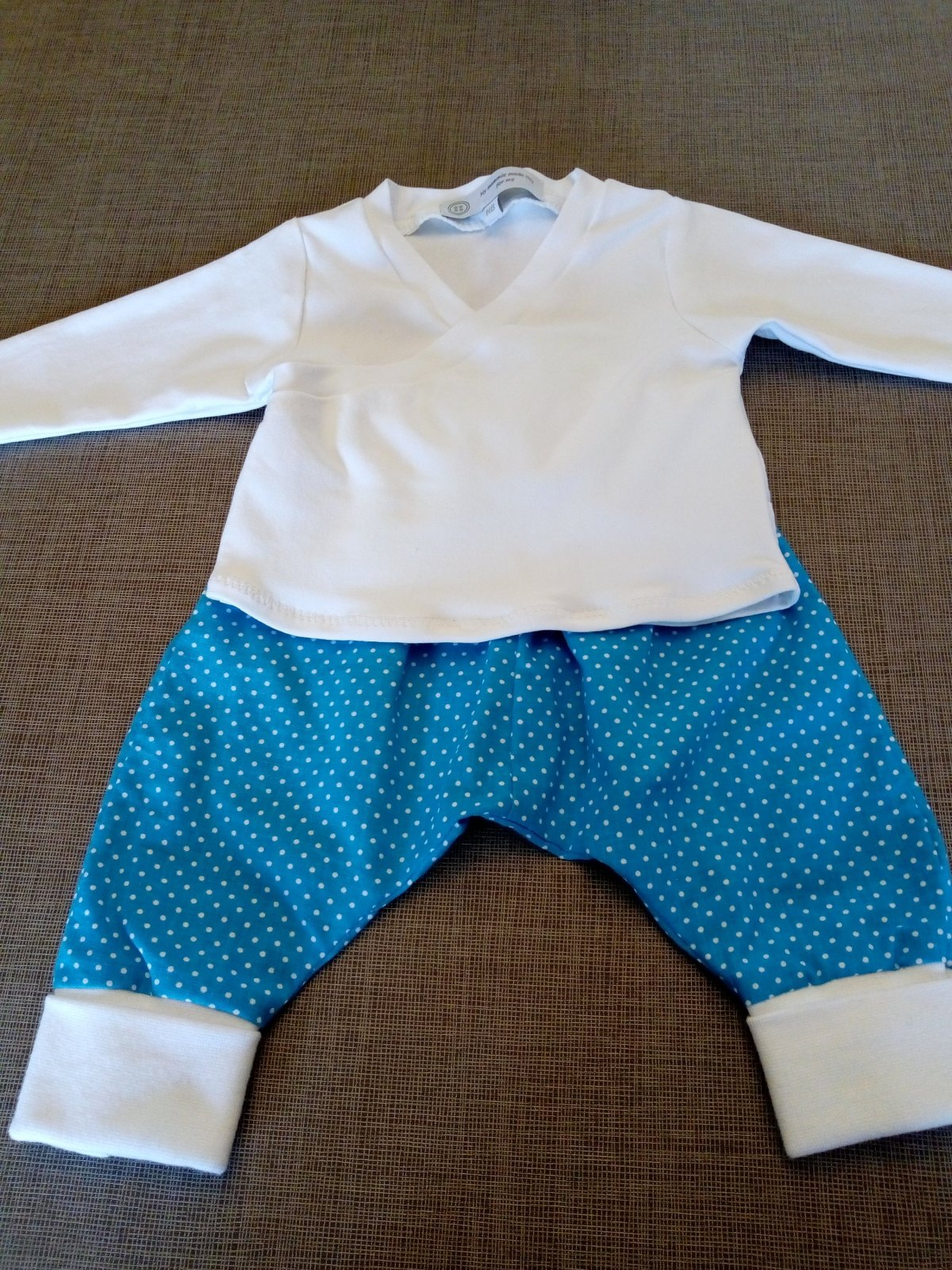 A flat-lay of a baby outfit, with blue and white spotted trousers and a white vee-neck top