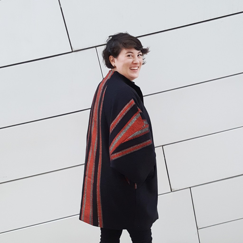 Light skinned woman with short dark brown hair wearing long robe-style coat that is black with red stripes.