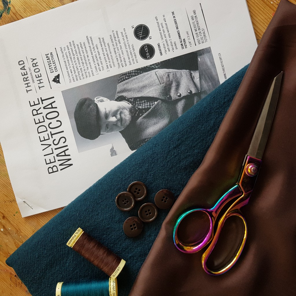 A photo of the Belevdere waistcoat instruction manual, teal wool fabric, brown lining fabric, rainbow scissors, brown buttons and teal and brown threads.