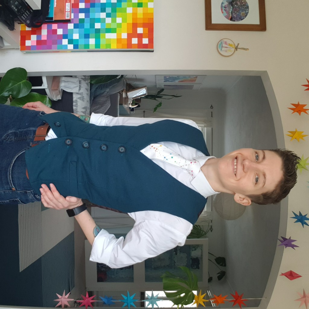A photo of the author, wearing the finished teal wool waistcoat, with a white shirt and a a white tie with rainbow constellations.