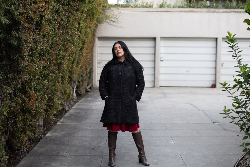 The author stands front on to the camera, hands in the pockets of a fitted black wool coat. A red knee-length skirt pokes out beneath the hem and tall boots complete the outfit.