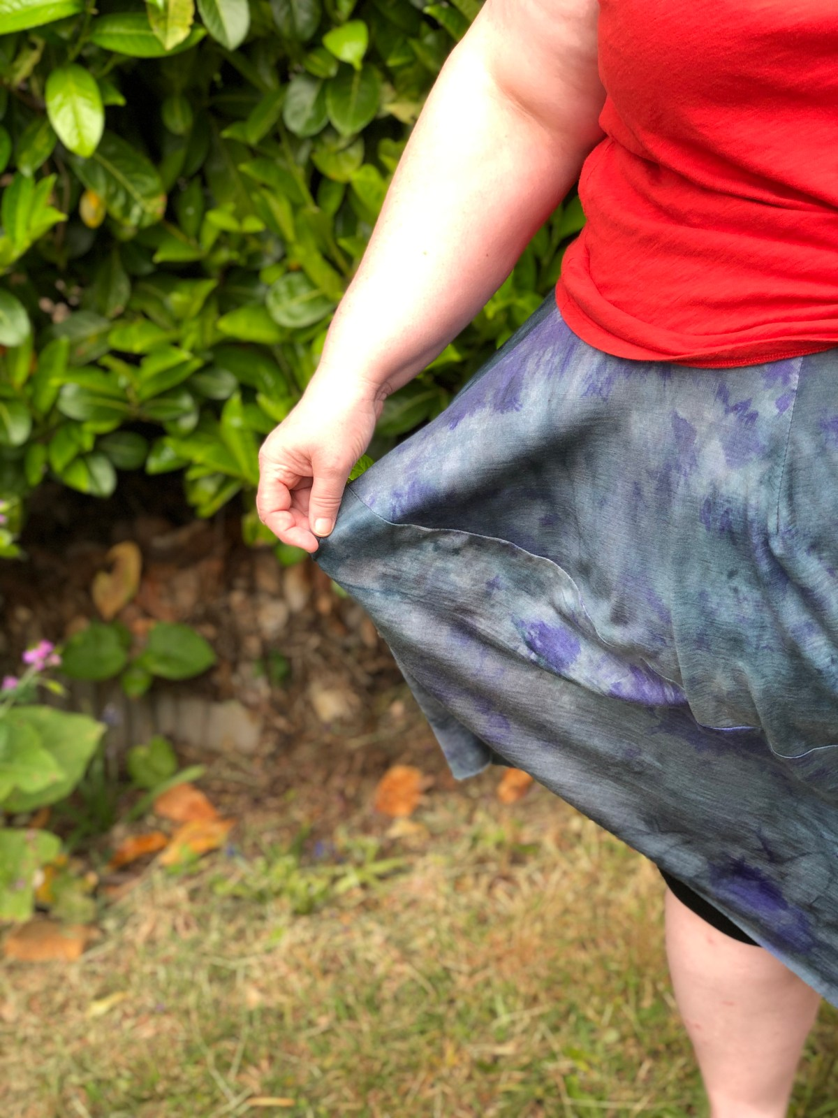 A detail of the skirt that highlights the drape of the fabric and its colors, blue, dark blue, and purple