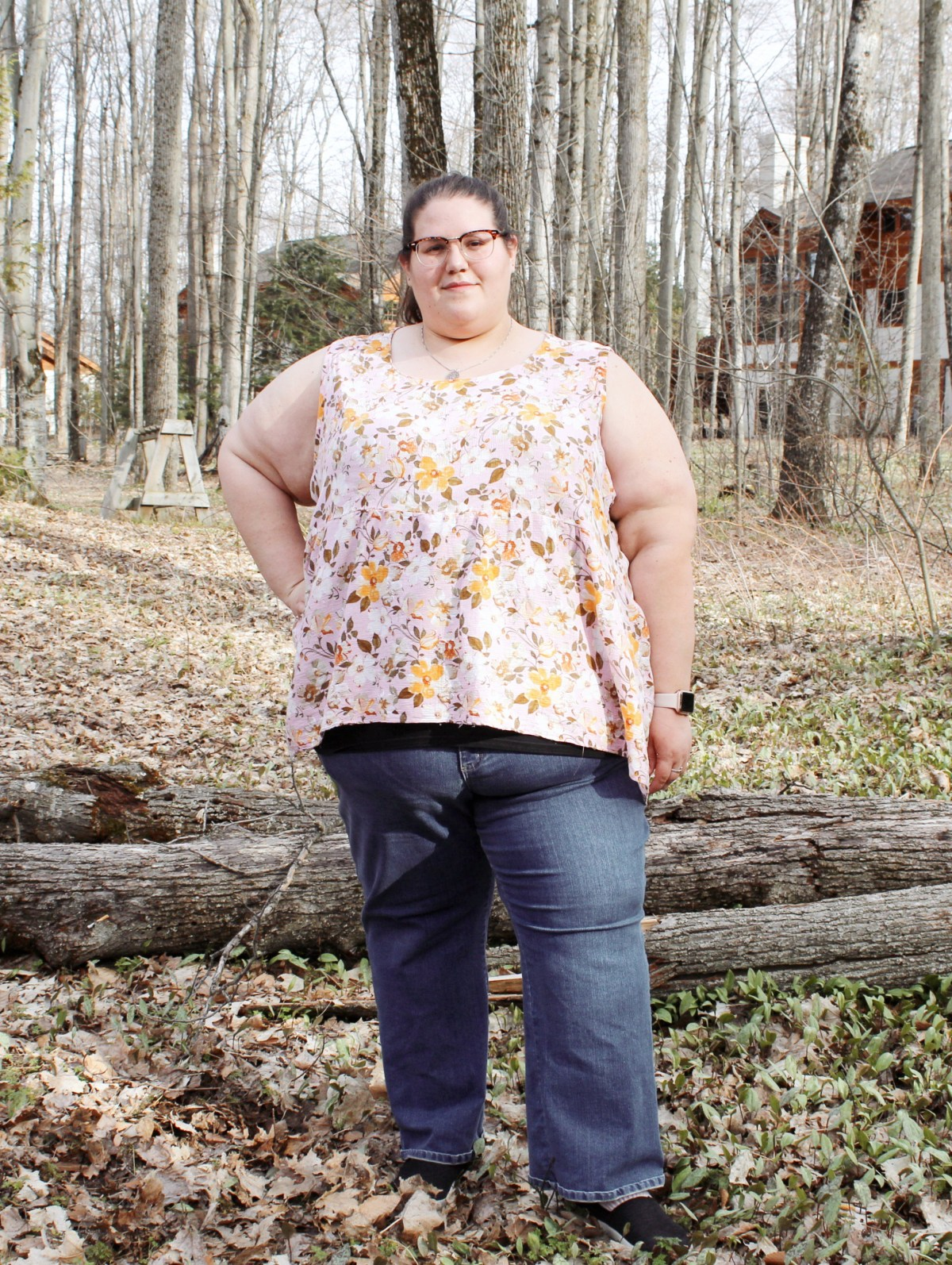 Jenn stands in front of three large tree limbs on leaf-covered ground; more trees and a house are behind her. She looks at the camera and smiles slightly, with her right hand on her hip. She wears blue jeans and a pink and yellow floral sleeveless top with a gathered lower bodice.