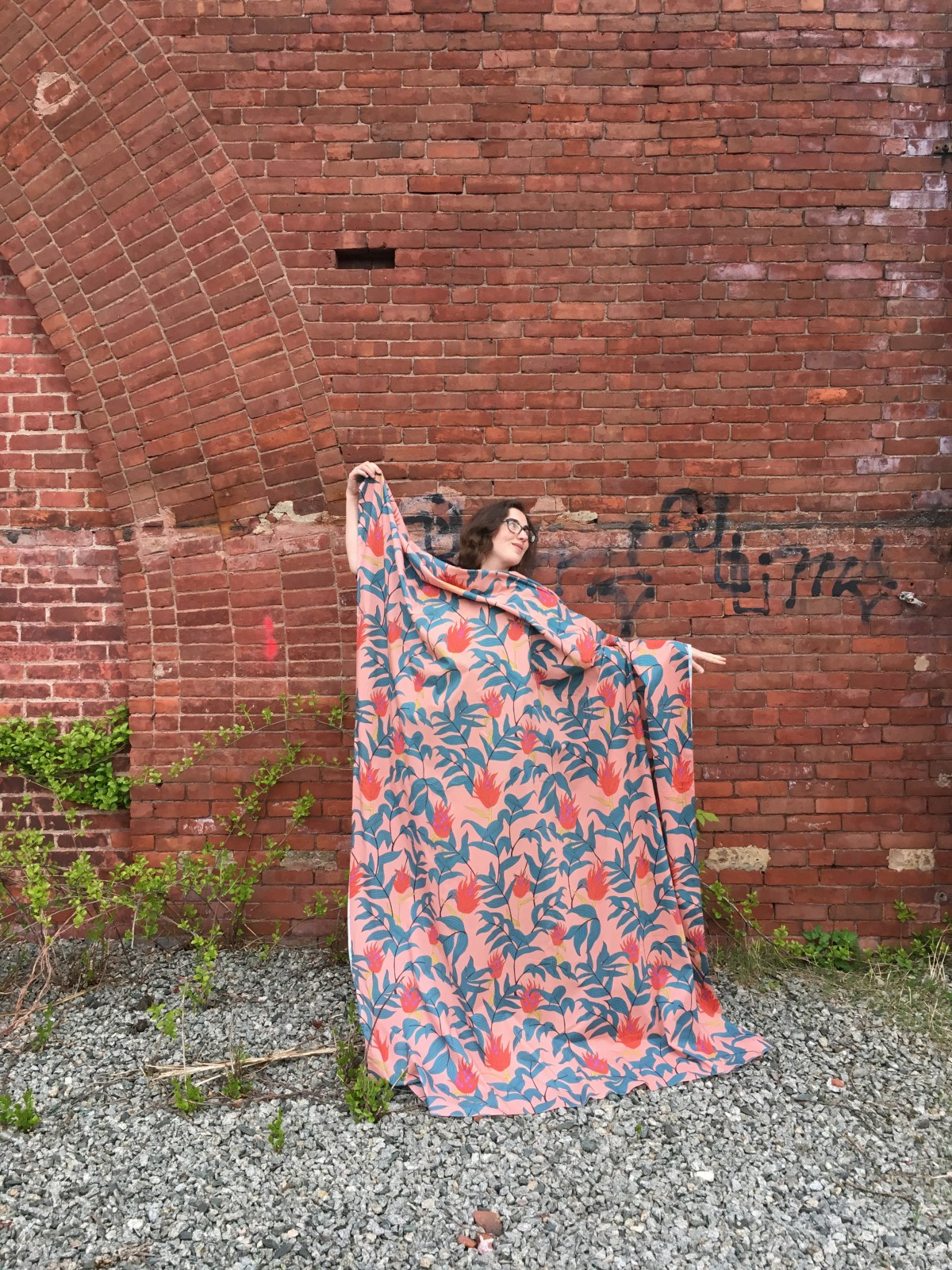 Author of post against a brick wall with light pink fabric with a large-scale red and green floral motif draped over her body