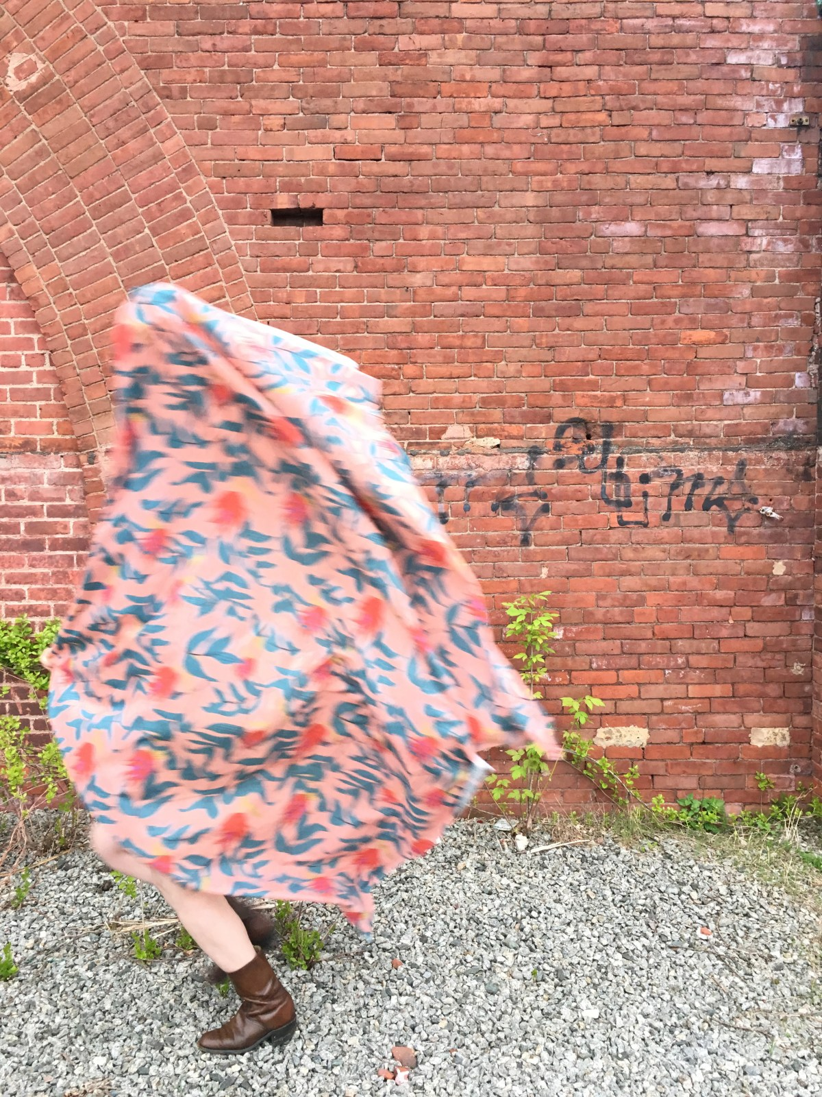 Author spinning light pink fabric with large-scale red and green floral motif like a cape around the body