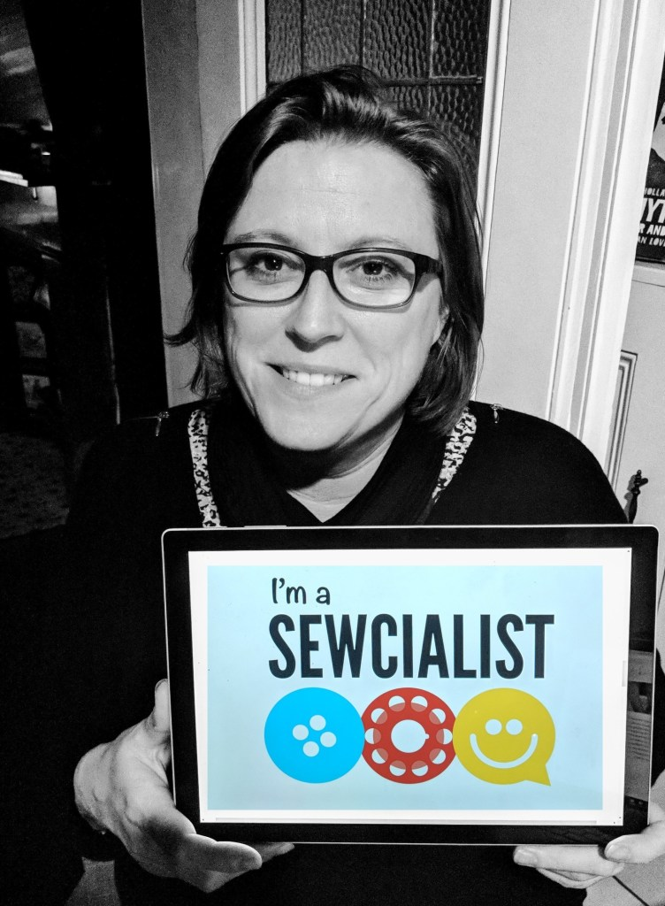 Sewcialists editor Chloe - in black and white and holding a computer with the Sewcialists logo on it.