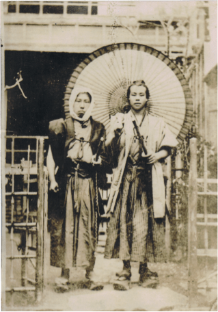 Two people in traditional Japanese dress, stand looking at the camera. One is holding a large umbrella.