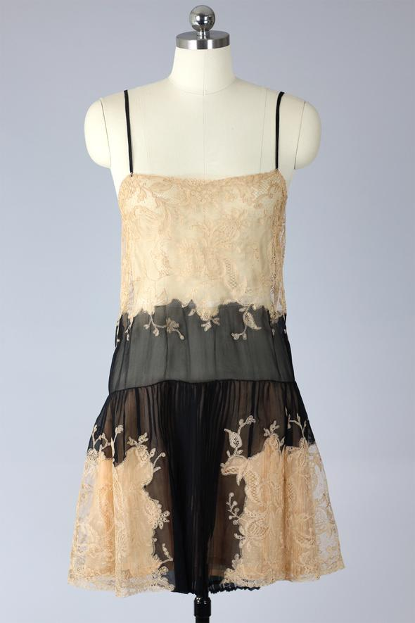 A mannequin displaying a knee length ivory and black slip with spaghetti straps, lace bodice, dropped waist and a pleated skirt made of sheer black chiffon and ivory lace