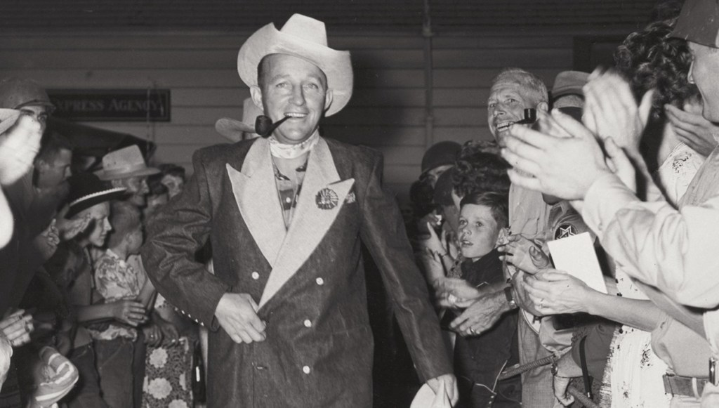 A black and white photograph of Bing Crosby striding through a crowd of applauding fans. He wears a stetson hat, a denim tuxedo suit and is smoking a pipe.