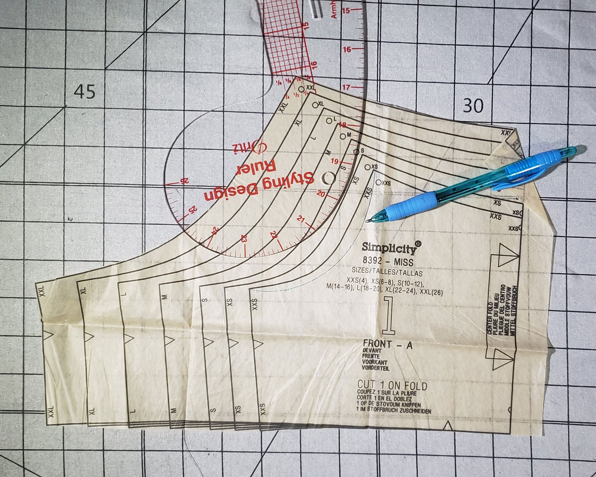 Pattern piece #1, the front, of the sports bra from Simplicity 8392 is laid out on a white, gridded cutting surface. A curved ruler sits on top of the armhole area, with a blue pen nearby. The pattern piece is ready to be altered.