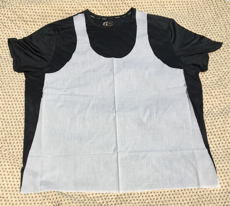 Image of a men's black T-shirt with the pattern for an A-line slip placed on the shirt.