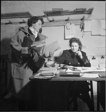 Two women in a war office in Britain, 1944. One woman is seated and on the telephone; another woman, standing, brings an armful of documents. The seated woman is in uniform, while the standing woman is in a duffel coat and carries her gloves.