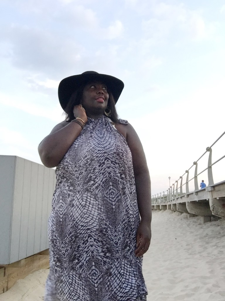 Photo of writer on a beach, wearing a large floppy hat and halter-style beach coverup dress.