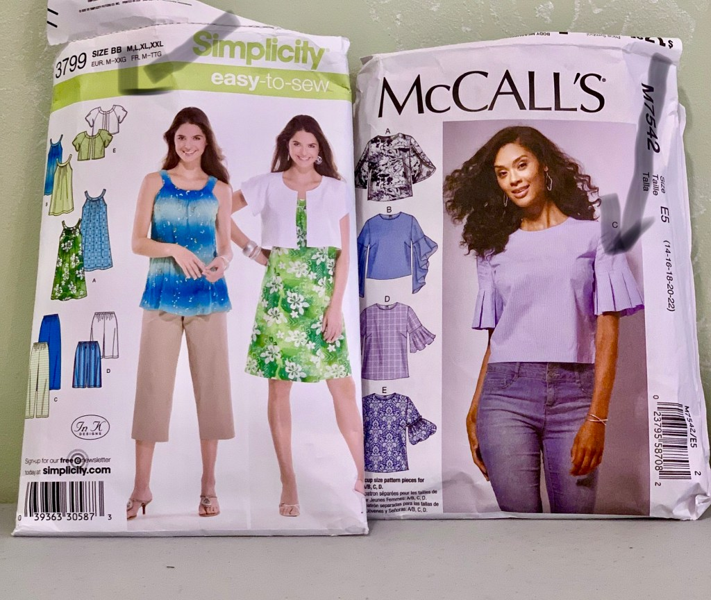 Two gray arrows overlaid on a photo of the pattern envelopes, with one pointing to Simplicity 3799  view E, short raglan sleeved crop jacket and the other to view C pleated lower sleeve on McCall's 7542
