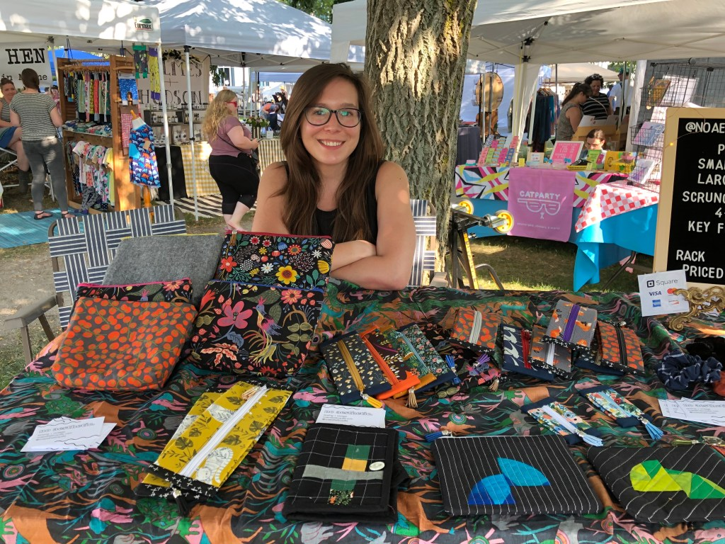 Francesca sits at a table of her sewn pouches at a craft fair, smiling for the camera.