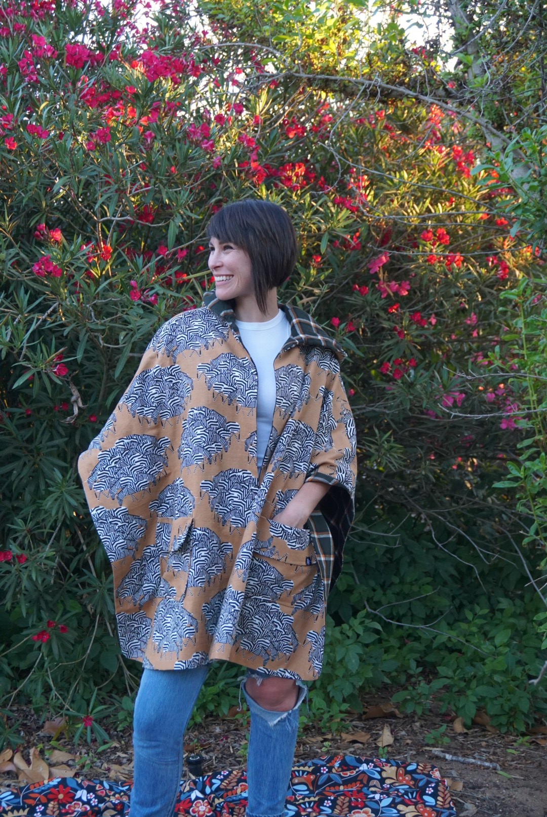 Mary smiles while posing in her new poncho. She has her left hand in the poncho's front pocket.