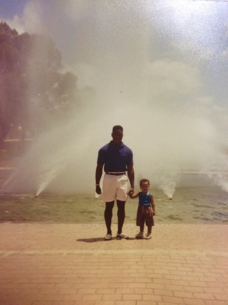 Image of father and toddler in front of a water fountain in Australia.