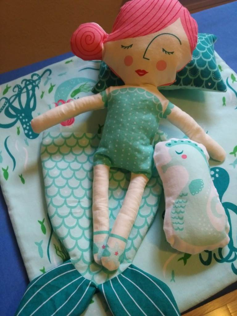 The mermaid doll, with pillow, bedspread, and seahorse stuffed animal. She is lying on her mermaid tail, which is sewn but hasn't yet been threaded with ribbon to gather it at the waist.