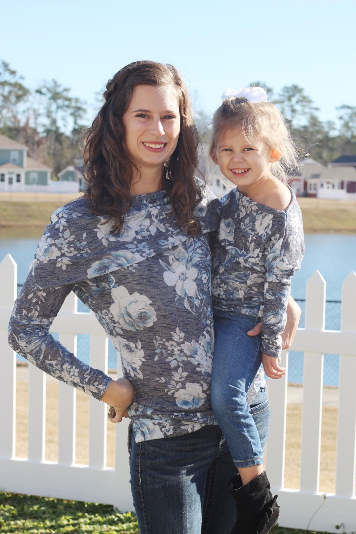 Tiffany, a woman with shoulder-length brown hair, and her daughter pose in front of a white picket fence that surrounds a pond. Tiffany holds her daughter on her left hip as they both smile into the camera. They are wearing matching off-the-shoulder sweaters made from gray fabric with a large-scale white and blue floral motif.