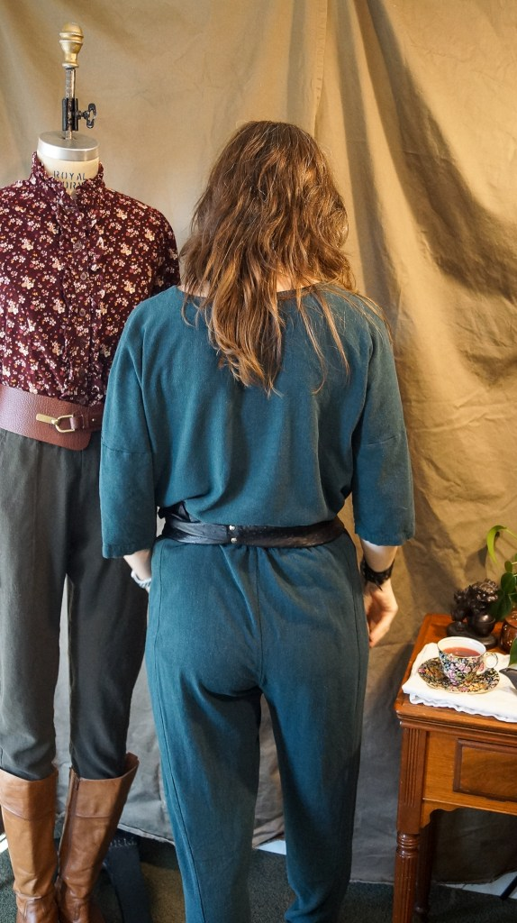 Brunette in green faux jumpsuit and a goofy grin, back view