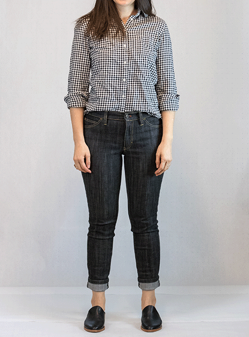 A young woman models the Workroom Social Claryville jeans. Her jeans are cuffed at the ankle, and she wears black leather shoes. Her jeans are paired with a black and white checked button-up shirt; her dark brown hair falls over her right shoulder.