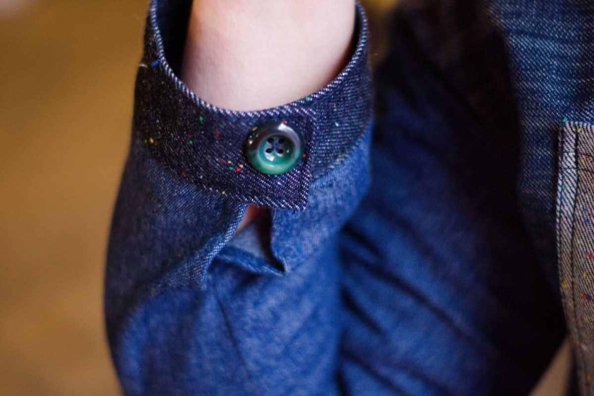 The photo shows a close up of a cuff of the denim jacket, it is two different shades of blue and has a green button.