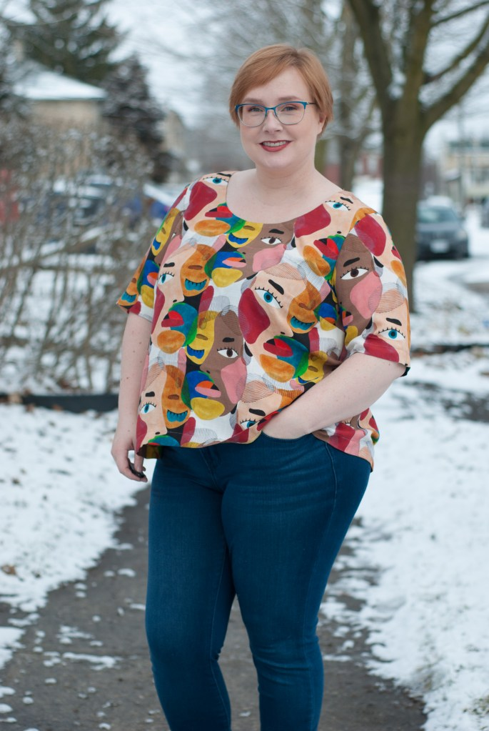 Gillian stands outside; it is winter, and there is snow on the ground. She faces the camera and is posing with her left hand in her front jeans pocket. Her top is a loose-fitting scoop-neck design, and features large-scale, multi-ethic faces and pops of bright pink, blue, and yellow on a white background.