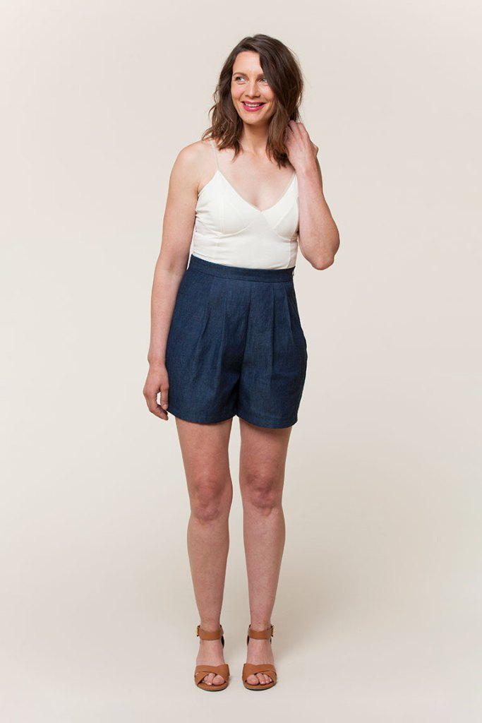 A model wears the Seamwork Heidi shorts, which are paired with an ivory knit camisole and tan leather sandals with a low heel. Her left hand lingers in her shoulder-length brown hair, and she is smiling.