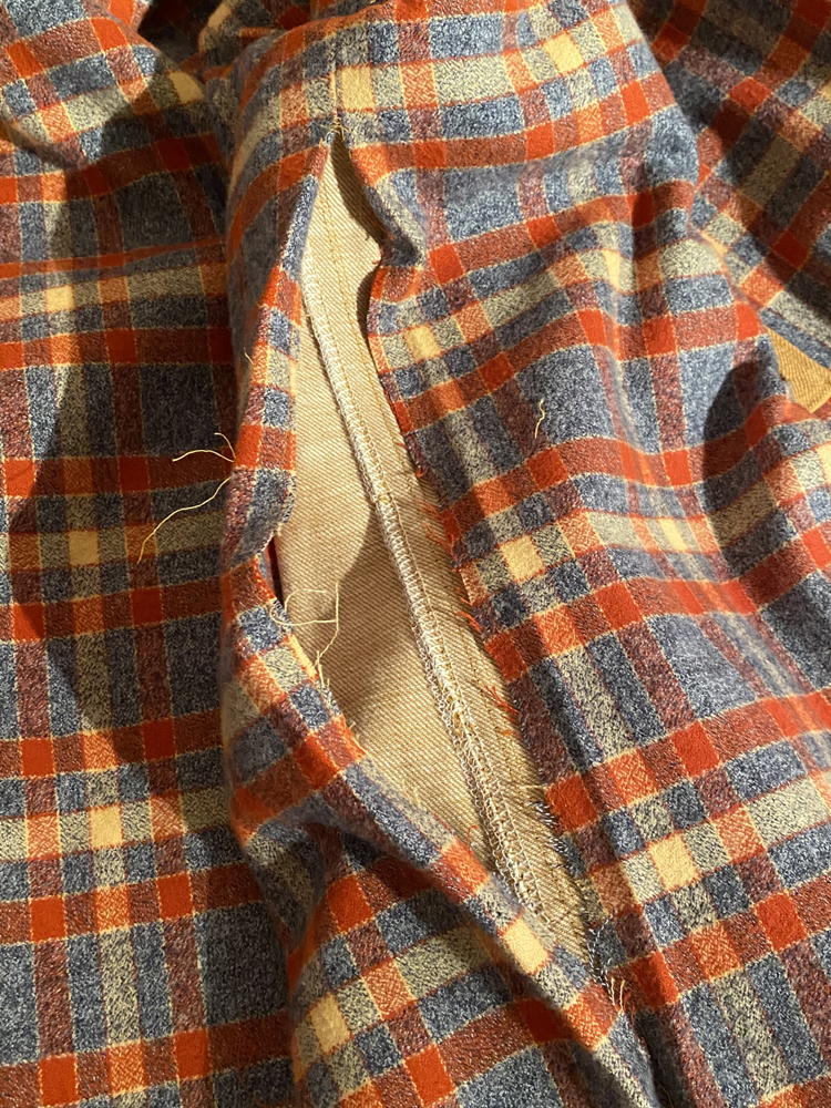 Liz's Sienna jacket is opened to show the lining; the seam in the lining is open, revealing the inside of the outer jacket shell beneath it. The seam is open in order to maneuver the jacket to bag the lining by machine.