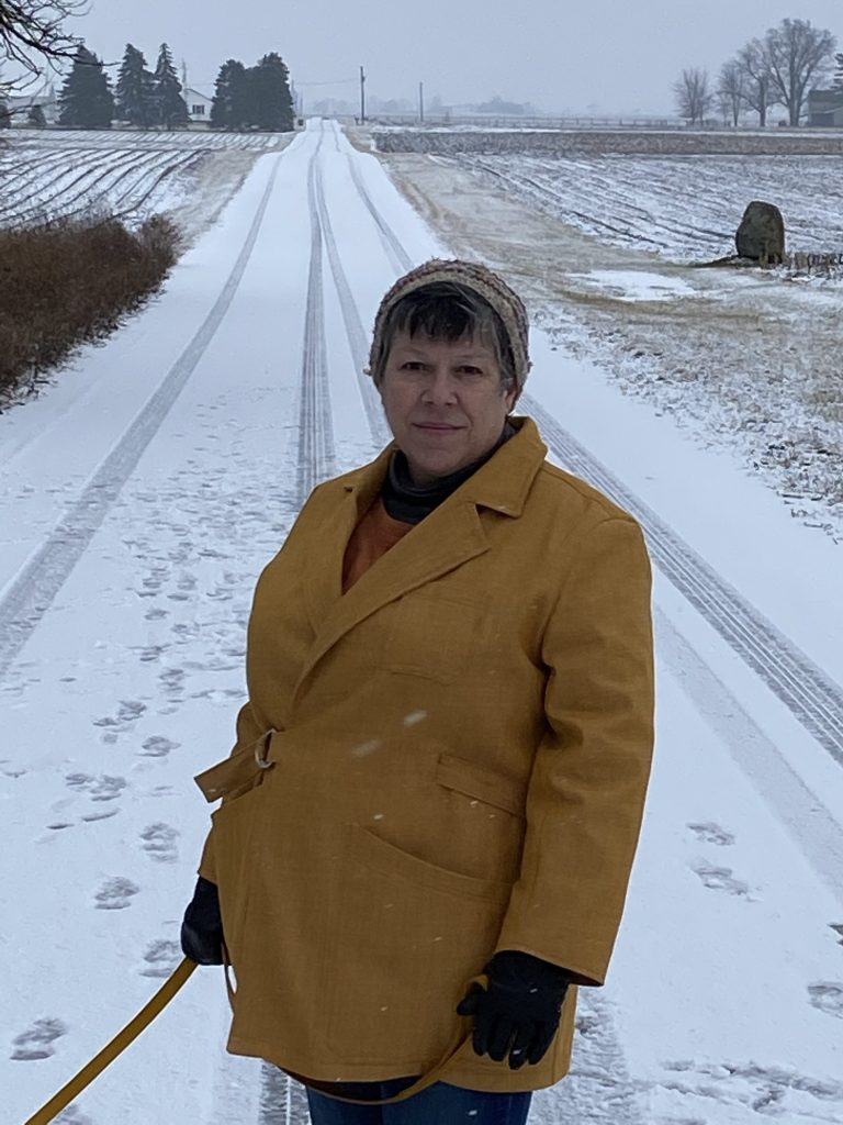 A closer photo of Liz wearing her Sienna jacket while walking her puppy. She stands in a snow-covered lane. Her goldenrod denim jacket features upper and lower pockets, and a belt that keeps it closed in the front. She is wearing a beanie hat and black gloves; it is snowing. She holds a leash in her hands, but the puppy is out of frame.